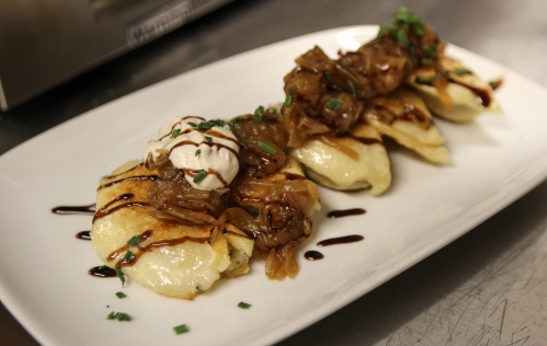 Pierogies covered in sweet caramelized onions and sour cream