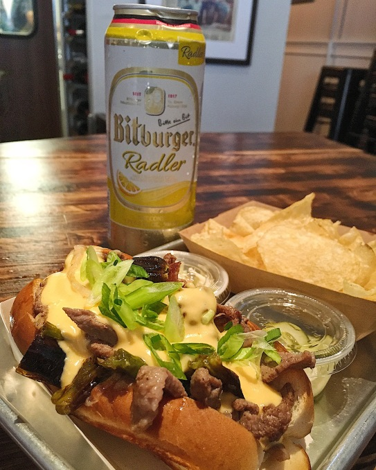Cheesesteak roll, refreshing radler in the back.
